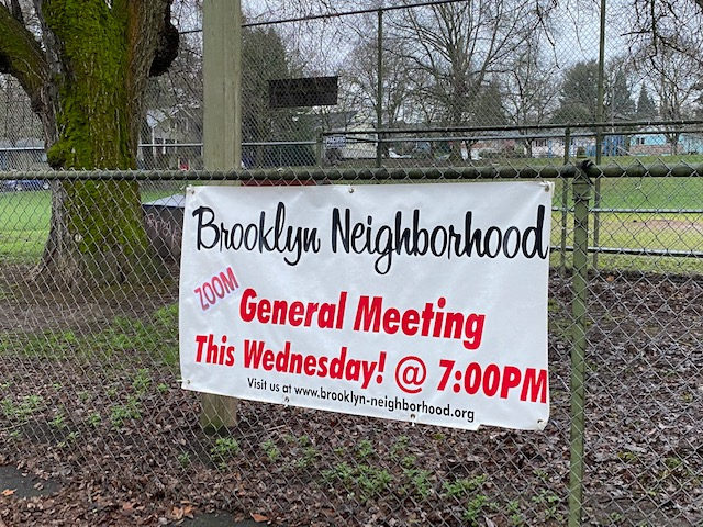 "Banner hanging on fence at Brooklyn Park announcing general meeting: ""Brooklyn Neighborhood, Zoom General Meeting this Wednesday! @ 7:00PM. Visit us at www.brooklyn-neighborhood.org."""
